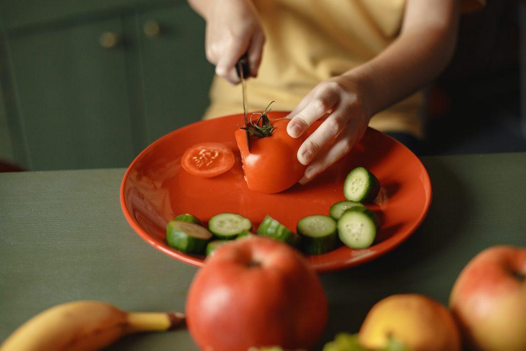 little boy cutting vegetables