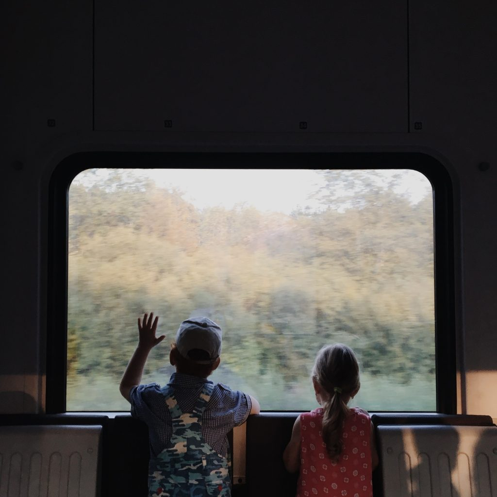 kids looking out window of train